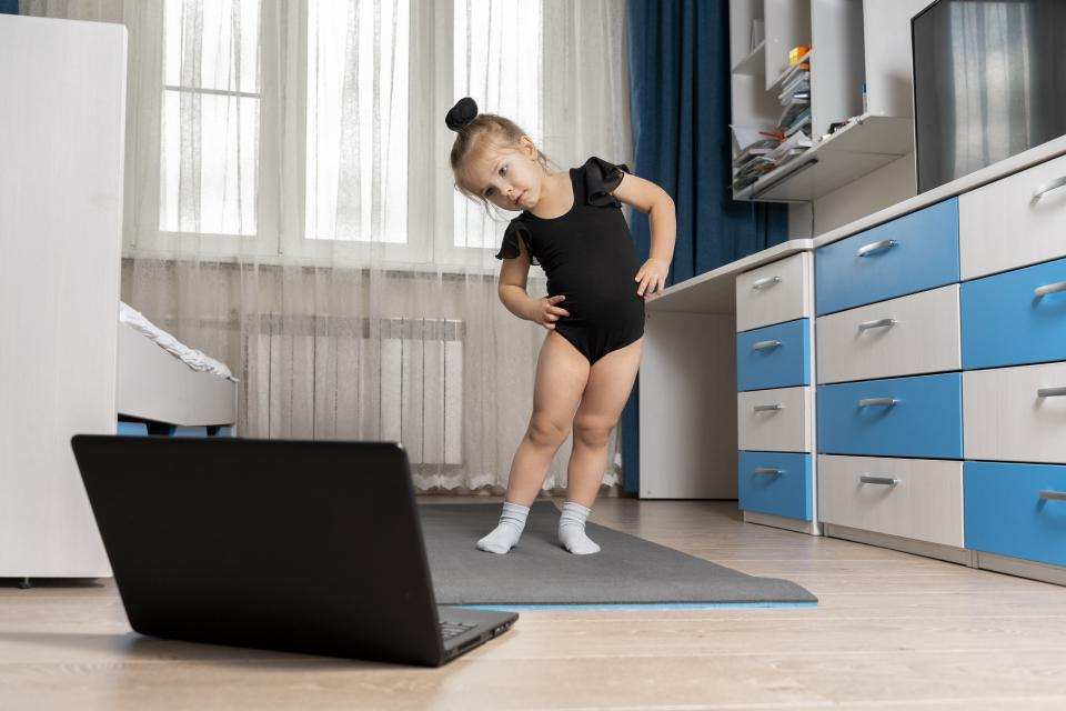 Little girl doing ballet in front of laptop computer