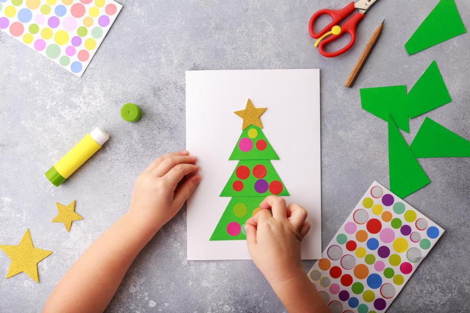 Child's hands making a homemade Christmas Card
