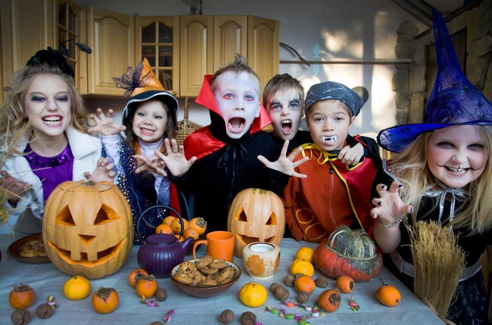 Photo of kids in costumes around pumpkins