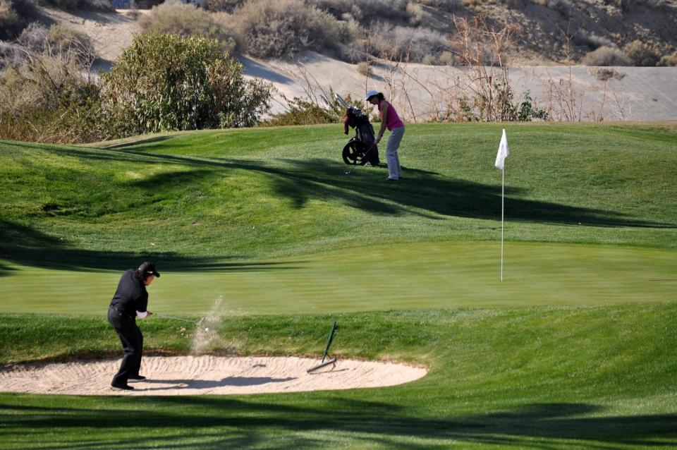 Golfer chips from the sand trap