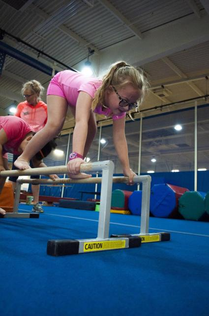 A girl with special needs on a gymnastics beam