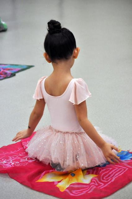 Photo of the back of a little girl in a ballet outfit