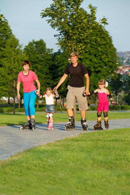 Man and woman holding hands with children rollerblading