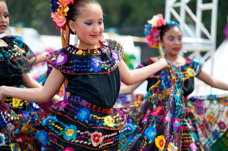 Child dancing folklorico in colorful outfit