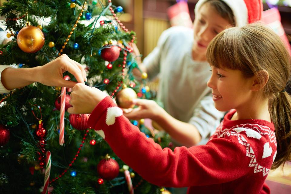 Child putting decorations on Christmas Tree