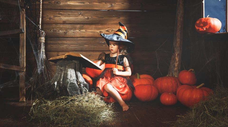 Little girl sitting among pumpkins with spell book