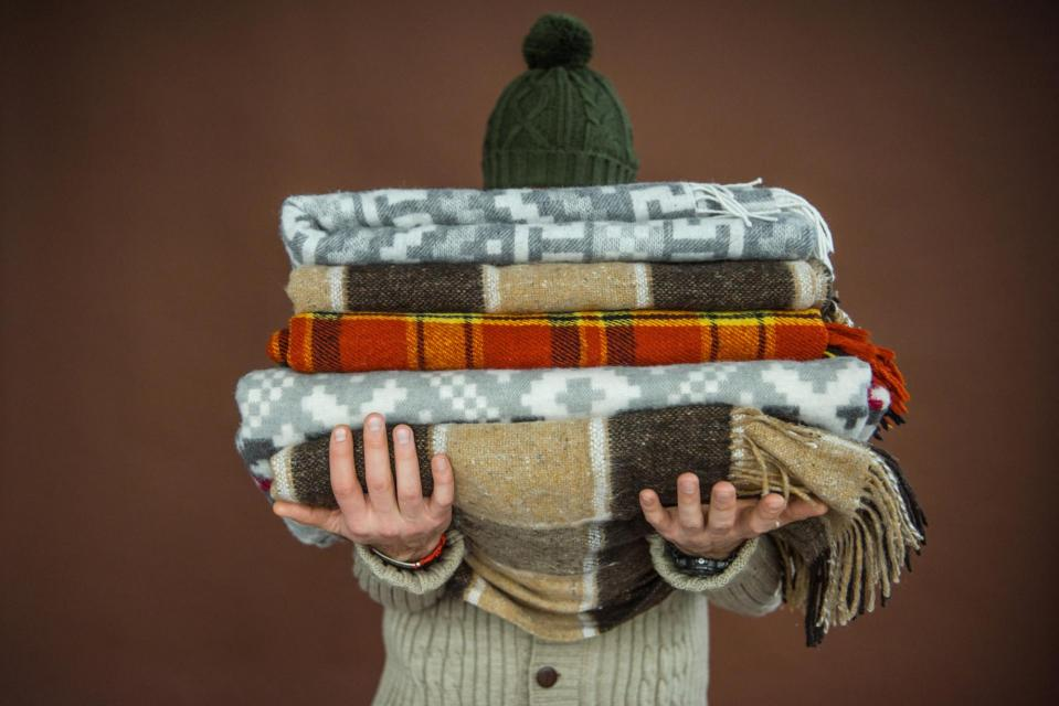 Person holding pile of blankets