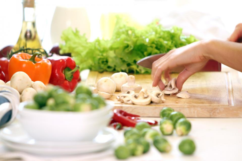 Hands chopping vegetables to cook