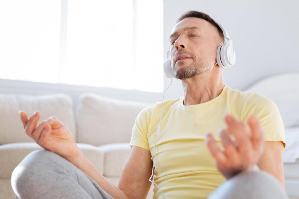 Man meditating with headphones on