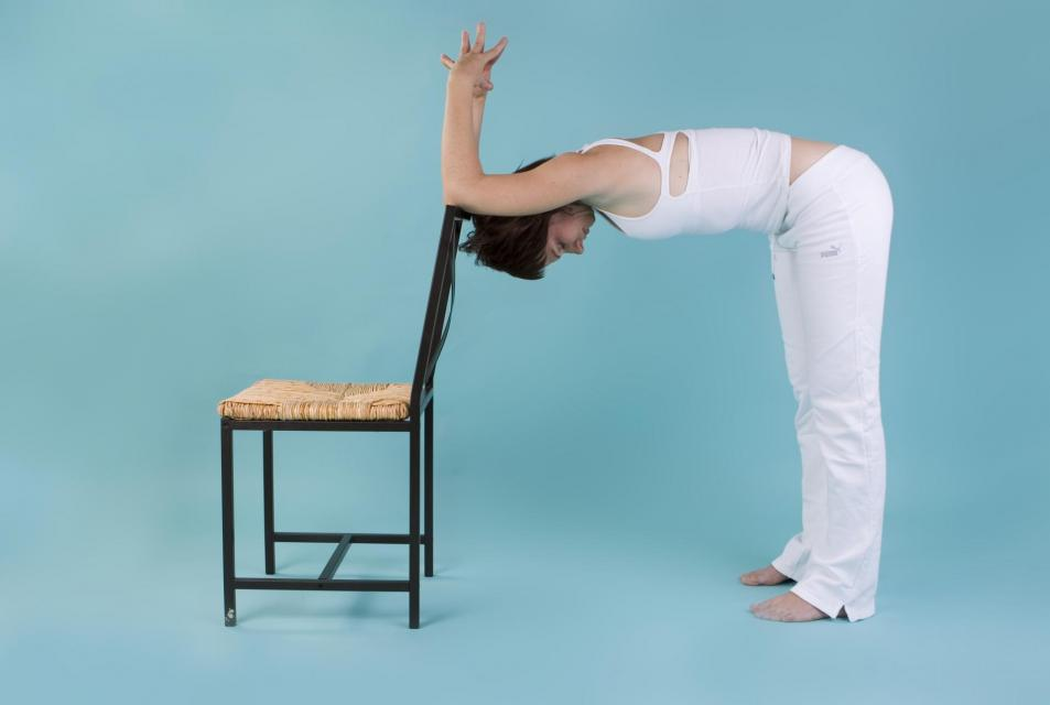 Person using a chair for assistance in yoga