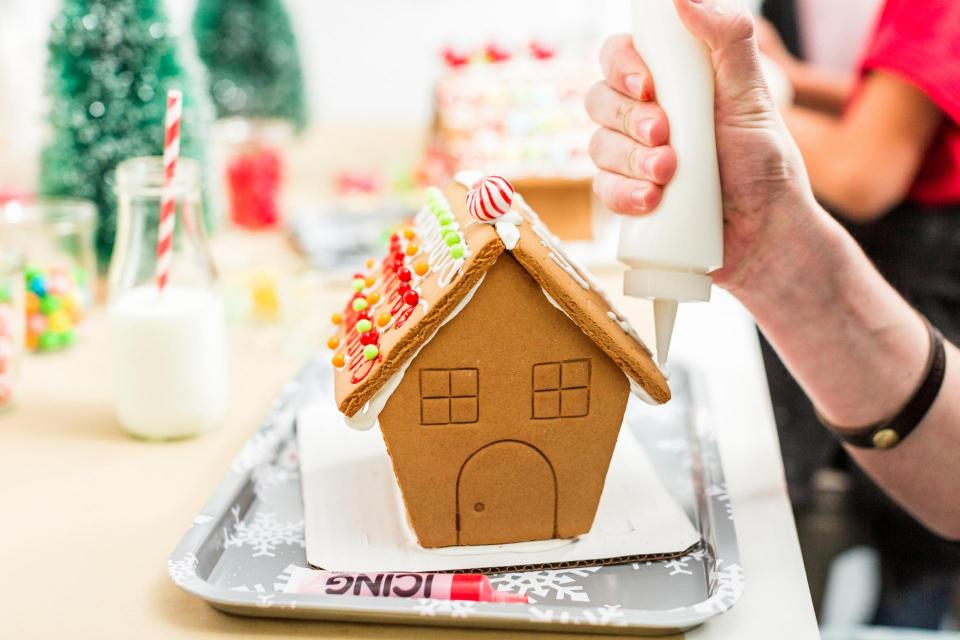 Hand decorating gingerbread house