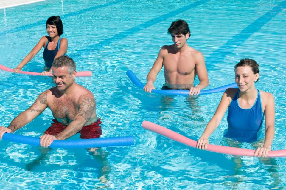 Adults doing water aerobics with noodles