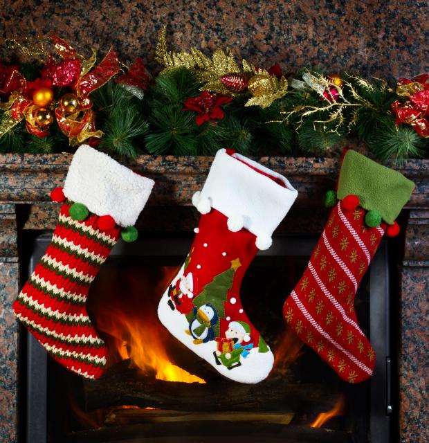 Three Christmas stockings hung by a fire