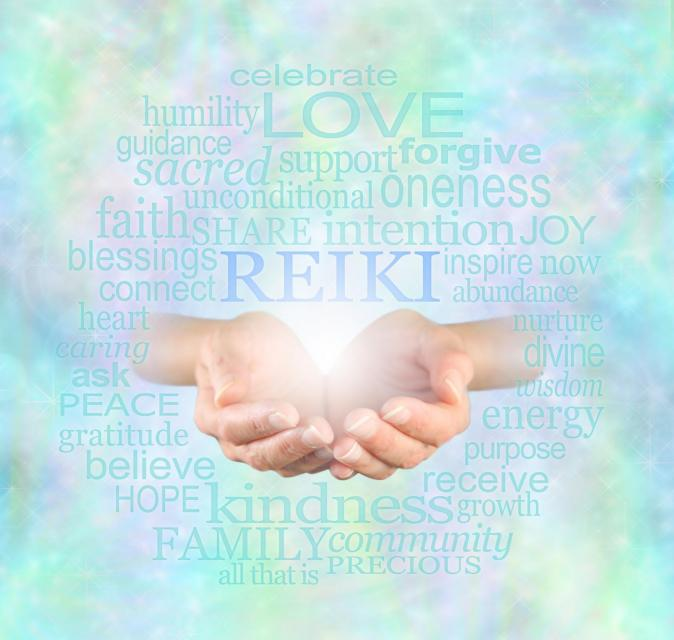Two open hands appearing to hold a light with the word Reiki