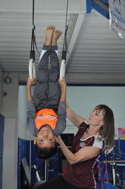 Boy hangs upside down on the gymnastics rings