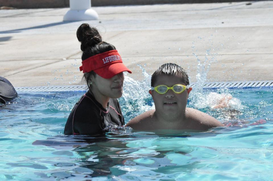 Adult helping child with special needs learn to swim in pool