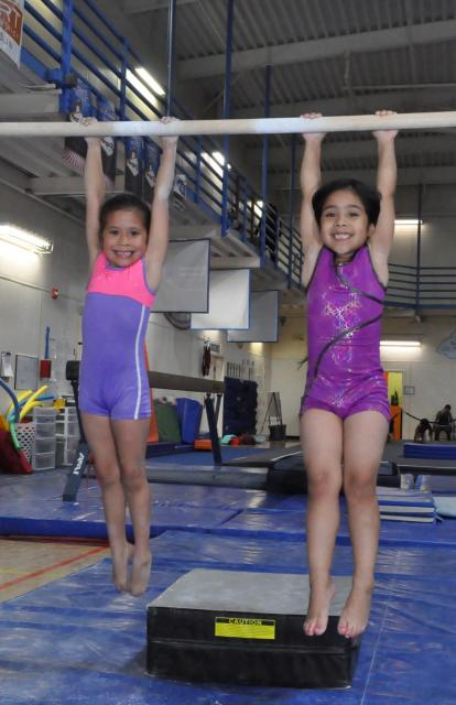 Girls hanging on the uneven bars