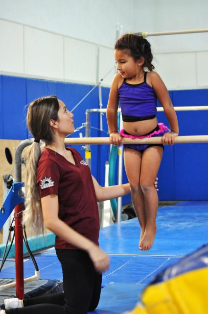 Gymnastics instructor trains student on the bars