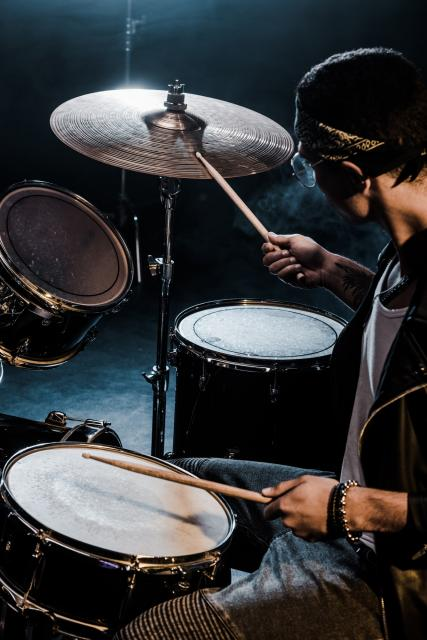 Side view of person playing drums