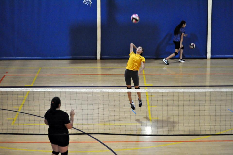 Volleyball players hitting a play indoors