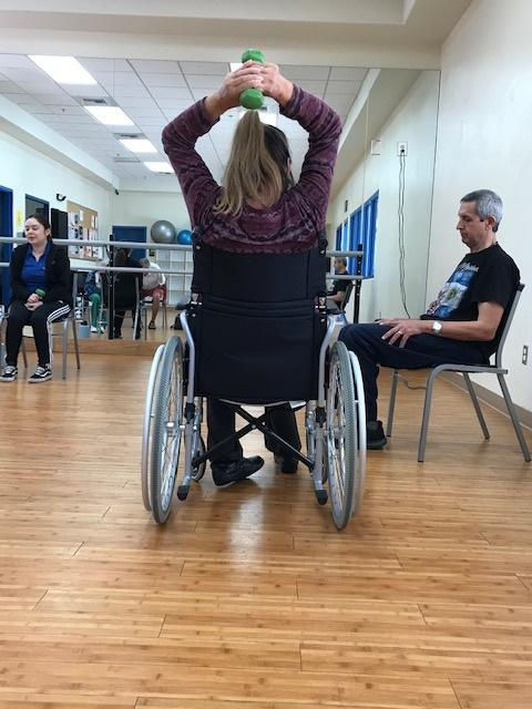 Woman in wheelchair exercising