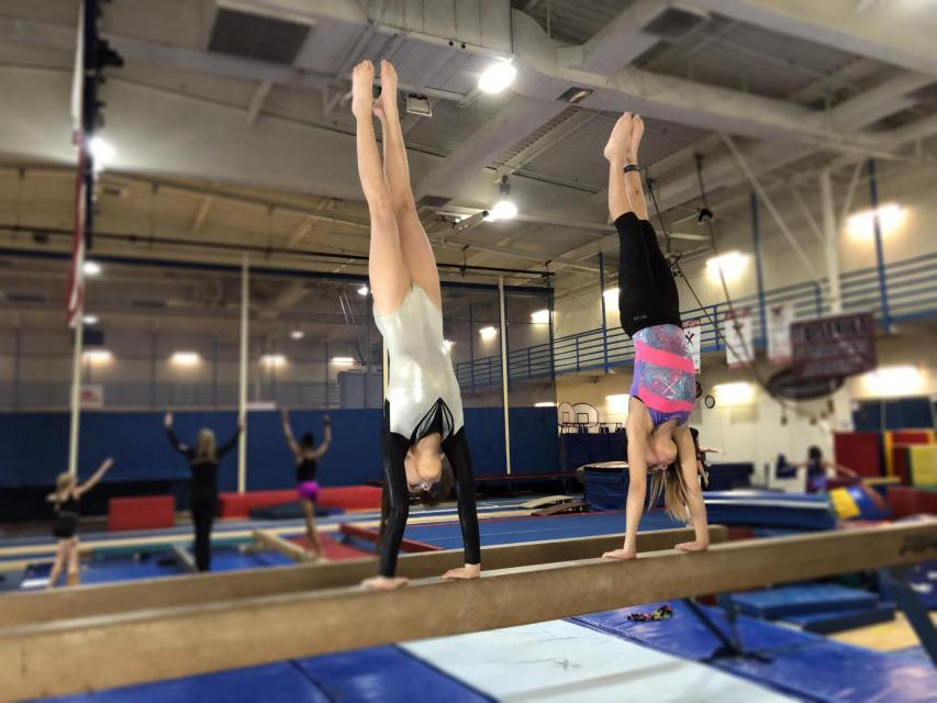 Two girls in a handstand on the balance beam