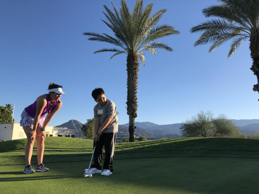 Photo of golf instructor with student putting