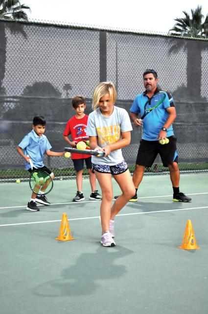 instructor and youth learning tennis
